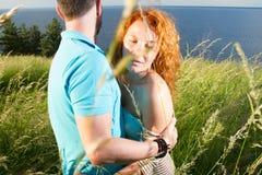 在热情地拥抱的爱的夫妇 两个恋人的期待已久的会议在近的湖之外 红色头发妇女和人 免版税库存图片