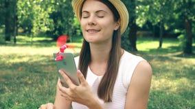 在热期间,变冷静与桃红色便携式的通风设备的女学生附有了手机 股票录像