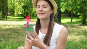 在热期间,变冷静与桃红色便携式的通风设备的女学生附有了手机 影视素材