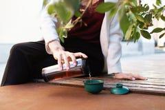 在热水瓶杯子的旅客女孩倾吐的茶,户外 在杯子的少妇饮用的茶 题材旅行 倾吐一份热的饮料的妇女在mu 免版税库存照片