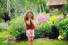 在热的夏日哄骗使用与庭院喷水隆头的女孩 免版税库存照片