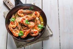 在热的平底锅供食的油煎的国王大虾 库存照片