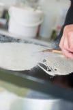 在热的平板炉的传播的绉纱有一块木刮板的 免版税库存图片