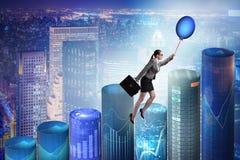 在热的气球的女实业家飞行在图表 图库摄影