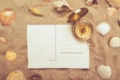 在热的海滩沙子和指南针的空白的明信片 图库摄影