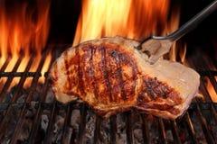 在热的火焰状烤肉格栅的猪腰牛排与叉子 免版税库存图片