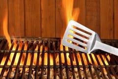 在热的火焰状BBQ格栅的小铲特写镜头 免版税库存图片