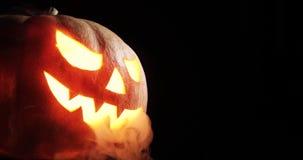 在热的灼烧的地狱火的可怕被雕刻的万圣夜南瓜发火焰 大helloween南瓜有与发光的一张疯狂的面孔 股票视频