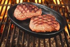 在热的BBQ火焰状格栅的两块牛排 库存图片