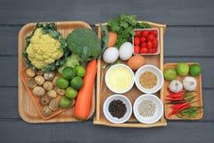 在烹调前的原料 包括菜、辣椒、蘑菇、大蒜、石灰和调味品 免版税库存照片