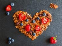 在烹调早餐蓝莓、草莓和格兰诺拉麦片的心脏形状的成份做由燕麦剥落,烘干了果子,坚果 图库摄影