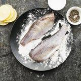 在烹调的新鲜的被毁坏的裁减河鱼与盐,胡椒,在灰色难看的东西背景的柠檬切片前 顶视图 免版税库存照片