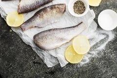 在烹调的新鲜的被毁坏的裁减河鱼与盐,胡椒,在灰色难看的东西背景的柠檬切片前 顶视图 库存照片