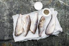 在烹调的新鲜的被毁坏的裁减河鱼与盐,胡椒,在灰色难看的东西背景的柠檬切片前 顶视图 图库摄影