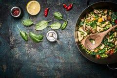在烹调罐的五颜六色的被蒸的健康菜有在土气背景,顶视图的成份的 免版税图库摄影