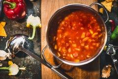 在烹调罐的热的墨西哥辣汤有在土气厨房用桌背景的杓子的 库存图片