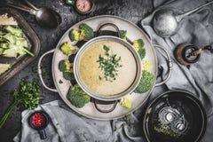 在烹调罐的硬花甘蓝汤在与成份和工具的土气厨房用桌背景 图库摄影