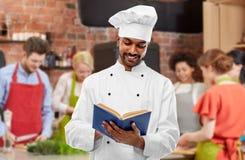在烹饪课的男性印度厨师读书菜谱 库存图片