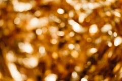 在焦点外面的金背景 库存照片