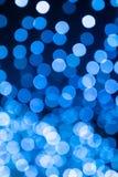 在焦点球外面的抽象欢乐蓝色bokeh在黑backgrou 库存照片