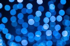 在焦点球外面的抽象欢乐蓝色bokeh在黑backgrou 免版税图库摄影