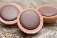 在焦糖的一颗榛子用乳脂状的牛乳糖和巧克力在木背景 库存照片