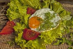 在煎蛋的煎蛋在莴苣叶子在委员会的 免版税库存图片