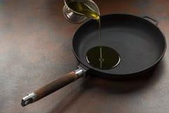 在煎锅的厨师倾吐的油 库存图片