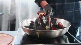 在煎锅的发出嘘声的淡菜 与油和调味料的厨师混合的海鲜 影视素材