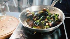 在煎锅的发出嘘声的淡菜 与油和调味料的厨师混合的海鲜 股票录像