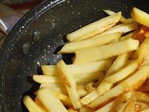 在煎锅的土豆片 库存照片