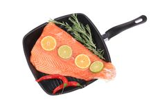 在煎锅的未加工的三文鱼用迷迭香 库存图片