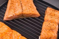 在煎锅的烤鲑鱼排 库存图片