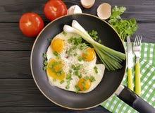 在煎锅的煎蛋,刀子土气叉子的早餐,葱,蕃茄,黑木背景 库存图片