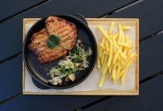 在煎锅的肉牛排用蘑菇和油煎的土豆平的视图 免版税库存照片