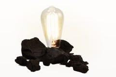 在煤堆的爱迪生样式电灯泡 免版税库存图片