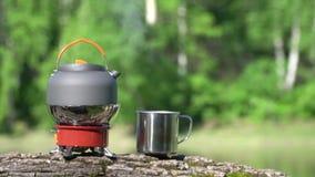 在煤气喷燃器上有茶壶 木头和湖的看法 影视素材