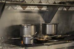 在煤气灶的平底锅在一家国际食物餐馆 免版税库存图片