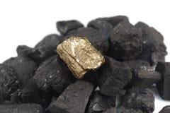 在煤炭背景的金黄矿块 库存图片