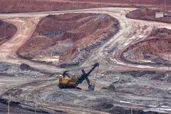 在煤矿的黄色反向铲工作 免版税库存照片