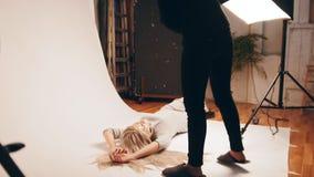 在照片演播室的可爱的白肤金发的式样女孩-摆在为摄影师 影视素材