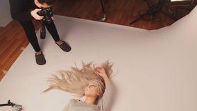 在照片演播室的可爱的白肤金发的式样女孩-摆在为摄影师 免版税库存图片