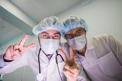 在照相机上的两位快乐的医生显示手标志和平 库存图片