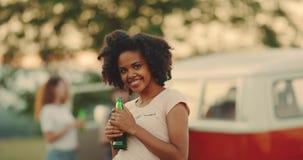在照相机前面的微笑的愉快的卷发非洲小姐饮用的啤酒在野餐 股票视频