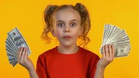 在照相机和微笑的快乐的女孩陈列美元束,第一收入 股票录像