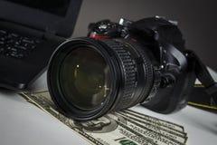 在照相机和膝上型计算机附近的很多美元 图库摄影
