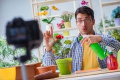 在照相机的人卖花人花匠vlogger博客作者射击录影 图库摄影