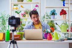 在照相机的人卖花人花匠vlogger博客作者射击录影 免版税库存照片