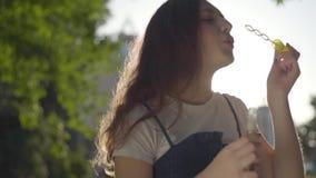 在照相机的十几岁的女孩吹的肥皂泡在公园在阳光下 单独逗人喜爱的年轻女人消费时间户外 股票录像