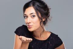 在照相机的妇女吹的亲吻 免版税图库摄影